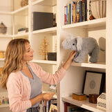 """15"""" Classic Elephant - Side view of standing gray plush elephant being placed on a shelf in a living room by a female model image number 6"""
