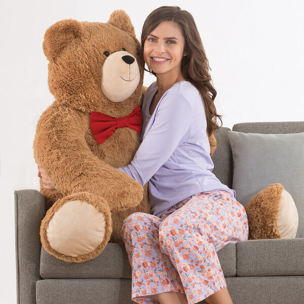 4' Big Hunka Love Bear with Bow Tie - front seated view of honey brown bear with a red velvet bow tie on a couch with a model in pajamas image number 0