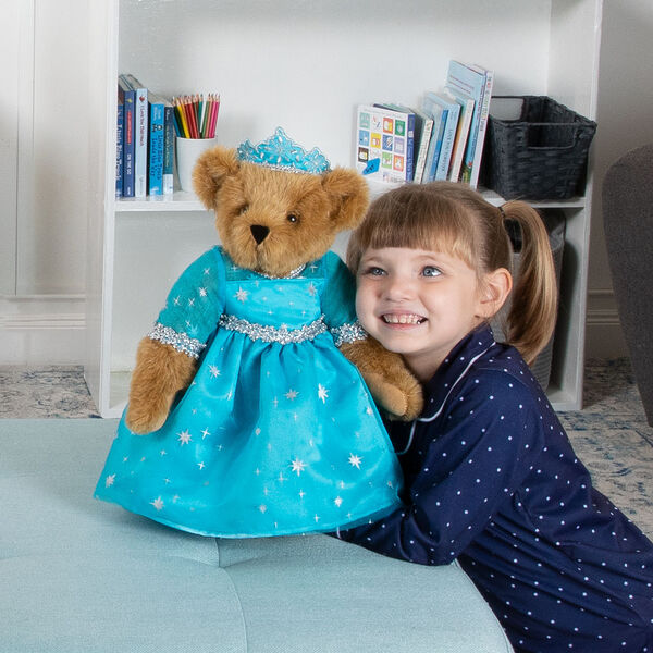 "15"" Winterland Queen Bear - Three quarter view of standing jointed bear dressed in a blue dress with silver star tulle overlay and silver lace trim and blue and silver tiarain a bedroom being held by a child in navy pajamas image number 2"