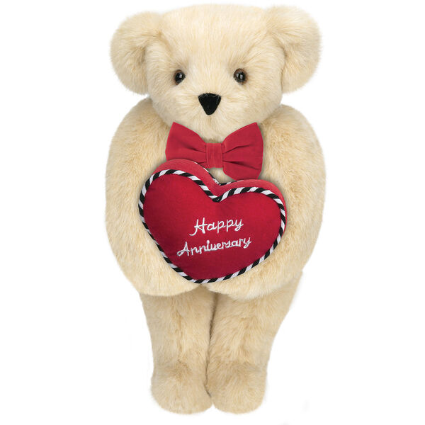 """15"""" Happy Anniversary Bear - Front view of standing jointed bear dressed in a red velvet bow tie and holding a red heart pillow that says' Happy Anniversary"""" in white  - Buttercream brown fur image number 1"""