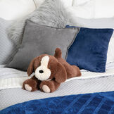 "15"" Belly Puppy Dog - Three quarter view of German Chocolate Bear with tan muzzle lying on its belly. Dog is snuggled on a bed with pillows image number 0"