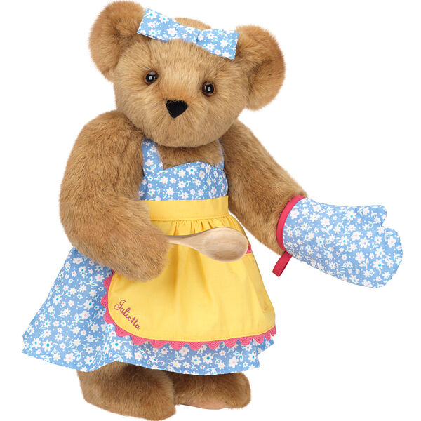 """15"""" Cooking Bear - Three quarter view of standing jointed bear dressed in a blue floral sundress and oven mitt, yellow apron with pink trim and holding a wooden spoon. Apron is personalized with """"Julietta"""" in hot pink - Honey brown fur image number 0"""