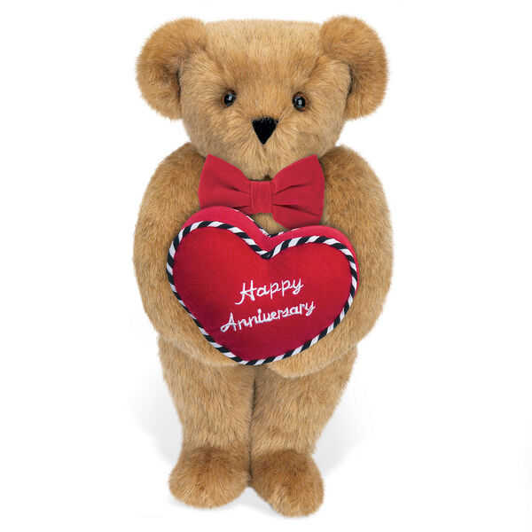 """15"""" Happy Anniversary Bear - Front view of standing jointed bear dressed in a red velvet bow tie and holding a red heart pillow that says' Happy Anniversary"""" in white  - Honey brown fur image number 0"""