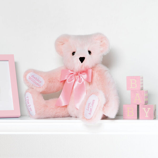 """15"""" Premium Baby Girl Bear - Front view of seated jointed pink bear with white paw pads and chose of eye color wearing a blue satin bow in a bedroom scene. image number 0"""