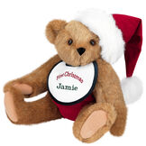"15"" Baby's First Christmas Bear - Seated jointed bear dressed in red velvet diaper with santa hat and white and green bib that says ' First Christmas' in red lettering. Bib is personalized with ""Jamie"" in dark green lettering - Honey brown fur image number 0"