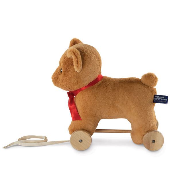"12"" Rolling Bear Toy - Side view of golden bear with red satin ribbon on wooden detachable wheel frame with pull cord image number 2"