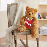 "20"" World's Softest Bear with Heart Pillow - 20"" seated golden brown bear with brown eyes holding a red fleece pillow with white diagonal sash. Pillow is personalized with ""Sarah"" in red lettering and is in a living room setting. image number 0"