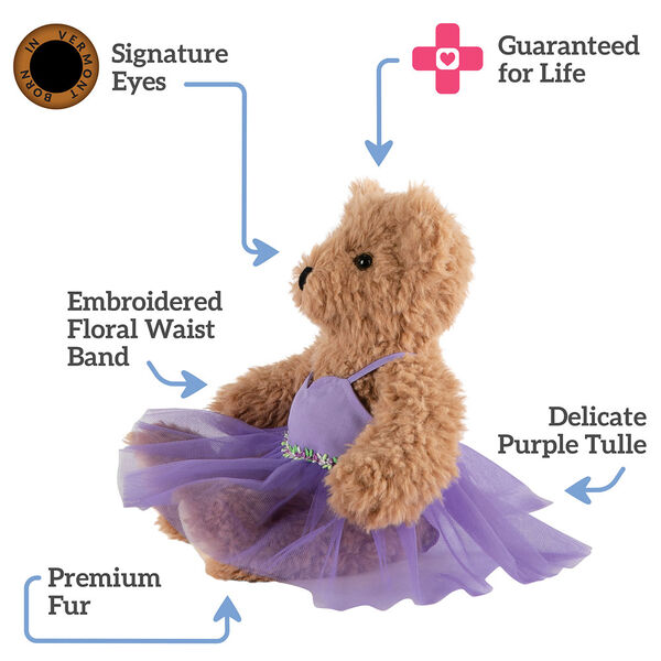 """13"""" Super Soft Ballerina Bear - Side view of seated Almond Brown Bear in purple ballerina dress. Text reads, """"Signature Eyes; Guaranteed For Life; Delicate Purple Tulle;  Premium Fur; Embroidered Floral Waist Band"""".  image number 1"""