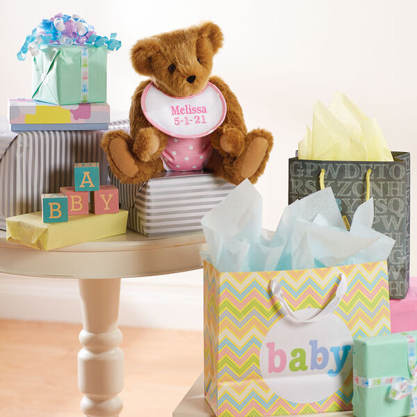 """15"""" Baby Girl Bear - Jointed honey bear dressed in pink with white dots fabric diaper and bib sitting on a table surrounded by gifts image number 2"""