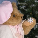 "15"" Bianca Bear - Side close up view of Jointed Bear in Honey Fur dressed in ivory cape with snowflake design and pink hat holding a snowflake image number 4"