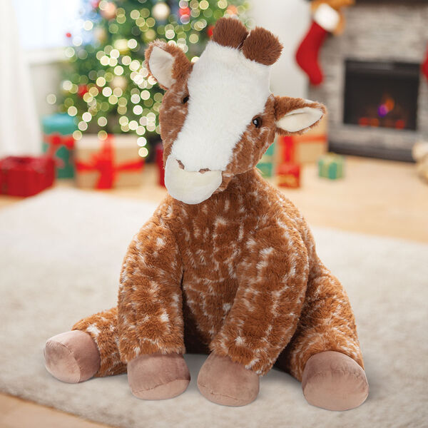 3 1/2' Gentle Giant Giraffe - Front view of seated soft giraffe in Christmas scene image number 0