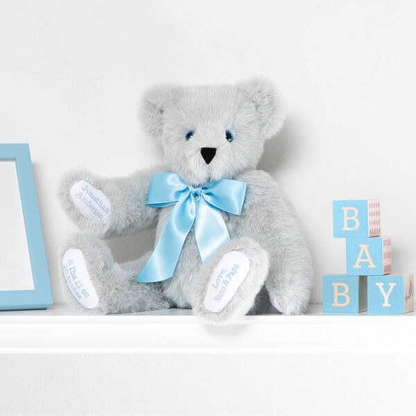 """15"""" Premium Baby Boy Bear - Front view of seated jointed gray bear with white paw pads and chose of eye color wearing a blue satin bow in a bedroom scene.  image number 0"""