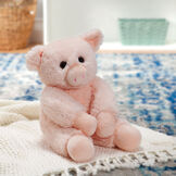 """18"""" Oh So Soft Pig - Three quarter view of seated soft plush pink pig with brown eyes and right ear folded down in a living room setting image number 3"""