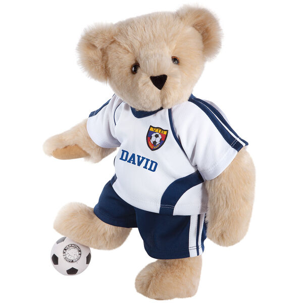 "15"" Soccer Bear - Three quarter view of standing jointed bear dressed in a blue and white jersey with VTB logo, blue shorts and comes with black and white soccer ball. Shirt is personalized with ""Emily"" on the front - Buttercream brown fur image number 1"