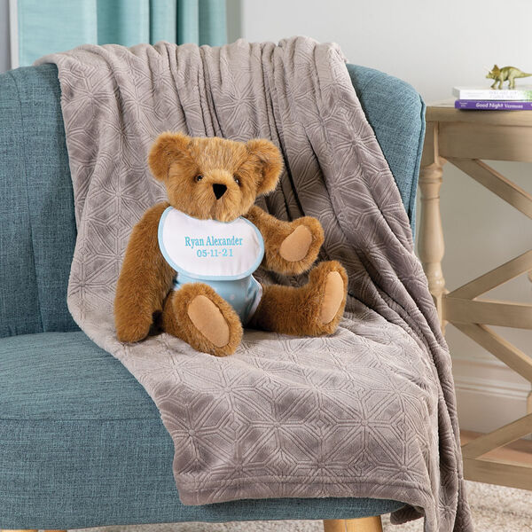"""15"""" Baby Boy Bear - Seated jointed bear dressed in light blue with white dots fabric diaper and bib on a chair in a living room setting image number 1"""