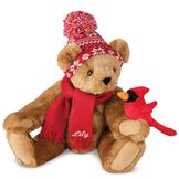 """15"""" Season's Greetings Bear - Front view of seated jointed bear dressed in a knit red and white nordic patterned hat with red scarf and holding a red cardinal. Bottom edge of scarf is personalized with """"Lily"""" in white lettering - Honey brown fur image number 0"""