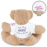 "15"" Spark Kindness Bear - Back view of seated soft caramel brown bear dressed in a white t-shirt with blue and purple graphics that says ""#KLCS"" surrounded by ""Kind, Loving, Caring, and Sharing""  image number 2"