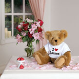 "15"" ""I HEART You"" Personalized T-Shirt Bear - Seated Jointed Honey Bear in white t-shirt that says I ""Heart"" Lauren in black and red lettering. Bear is seated on a table with flowers and chocolates and surrounded by flower petals.  image number 6"