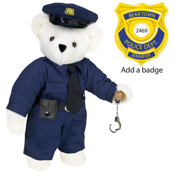 "15"" Police Officer Bear - Three quarter view of standing jointed bear dressed in a navy blue police uniform with shirt, pants, black tie and hat and holding handcuffs. Personalize with a Police badge - Vanilla white fur image number 2"