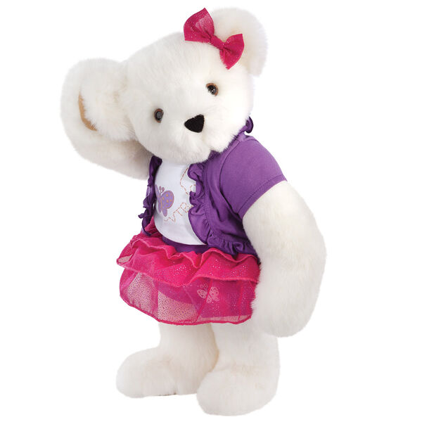 """15"""" Glitter Whimsy Bear - Three quarter view of standing jointed bear dressed in a pink skirt and hair bow, white shirt with butterfly graphic, purple shorts and sweater - Vanilla white fur image number 2"""