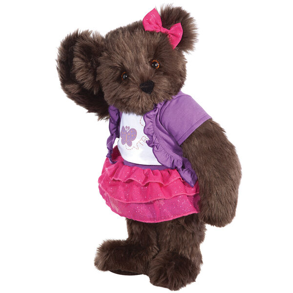 """15"""" Glitter Whimsy Bear - Three quarter view of standing jointed bear dressed in a pink skirt and hair bow, white shirt with butterfly graphic, purple shorts and sweater - Espresso brown fur image number 7"""