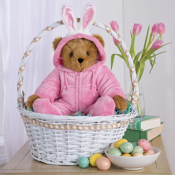 """15"""" Hoodie-Footie Bunny Bear - Front view of standing jointed bear dressed in pink hoodie footie and bunny ears sitting in an Easter basket surrounded by decorations image number 5"""