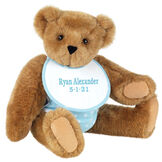 """15"""" Baby Boy Bear - Seated jointed bear dressed in light blue with white dots fabric diaper and bib. Bib with """"Ryan Alexander"""" and """"5-1-21"""" in light blue lettering - Honey brown fur image number 0"""