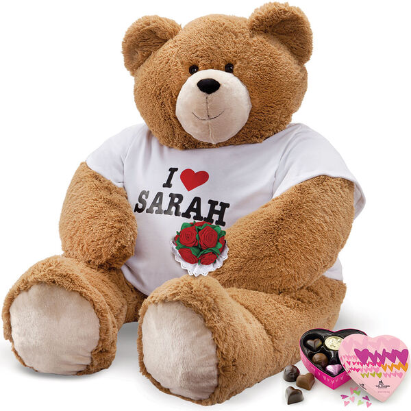"""4' Big Hunka Love """"I HEART You"""" T-Shirt Bear with Roses and Chocolates - Seated honey brown bear with brown eyes dressed in a white t-shirt with 'I Heart Sarah' personalized on the front in black and red, holding red velvet roses & heart box of chocolates image number 0"""