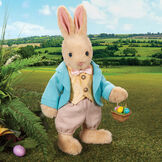"""16"""" Limited Edition Easter Bunny - Jointed Standing Buttercream Rabbit in a turquoise jacket, yellow vest with bow tie, tan knickers holding an Easter basket with eggs. Rabbit is in an outdoor setting.  image number 0"""