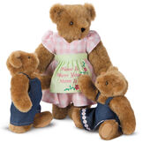 """15"""" Home Is Where Your Mom Is Bear - Front view of standing jointed bear wearing a pink gingham dress, green bow and apron with floral embroidery and says """"Home is Where Your Mom Is"""". Two honey cubs dressed in denim overalls and dress - Honey brown fur image number 0"""