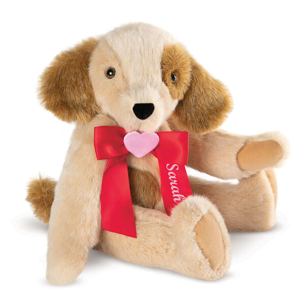 """15"""" Classic Puppy Dog - Front view of seated jointed tan puppy dog with honey brown spots, ears and taildressed in a red satin bow with pink heart in center personalized with """"Sarah"""" in white - Buttercream brown fur image number 0"""