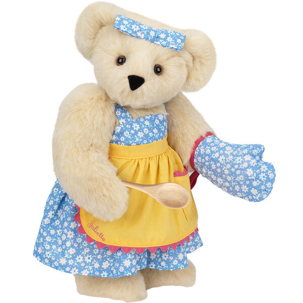"""15"""" Cooking Bear - Three quarter view of standing jointed bear dressed in a blue floral sundress and oven mitt, yellow apron with pink trim and holding a wooden spoon. Apron is personalized with """"Julietta"""" in hot pink - Buttercream brown fur image number 1"""