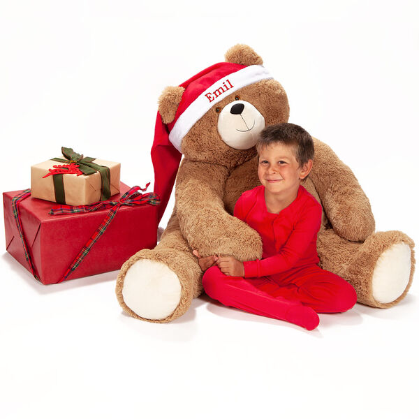 """Big Hunka Love Santa Hat - 4' bear's red velveteen hat with white fur trim personalized with """"Emil"""" on the brim on a seated honey brown bear  image number 1"""