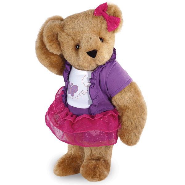 """15"""" Glitter Whimsy Bear - Three quarter view of standing jointed bear dressed in a pink skirt and hair bow, white shirt with butterfly graphic, purple shorts and sweater - Honey brown fur image number 0"""