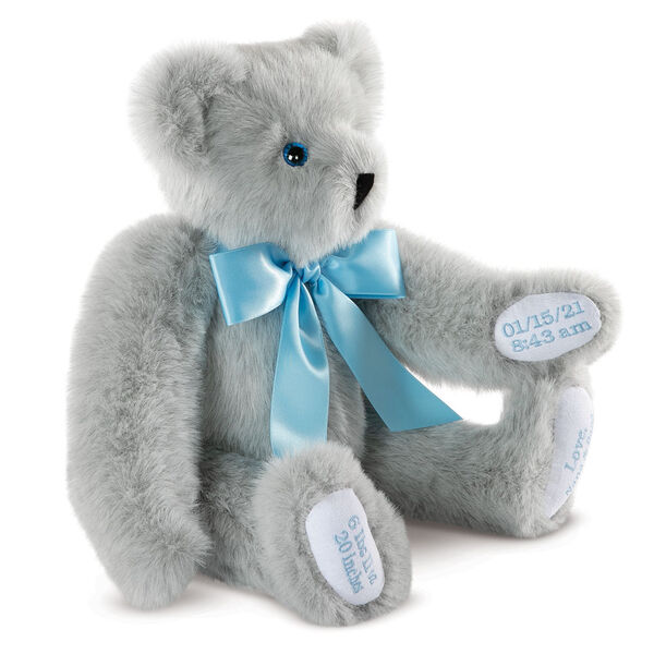 """15"""" Premium Baby Boy Bear - Three quarter view of seated jointed gray bear with white paw pads and chose of eye color wearing a blue satin bow. All 4 paw pads are personalized with baby's name, birth date, pounds and inches at birth. image number 2"""