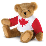 "15"" Maple Leaf Sweater Bear - Three quarter view of seated jointed bear dressed in white knit sweater with red maple leaf on front and red sleeves  - Honey brown fur image number 0"