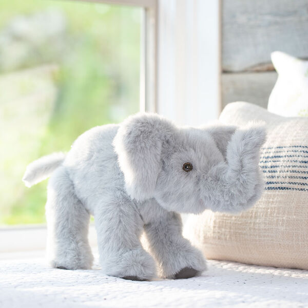 """15"""" Classic Elephant - Side view of standing gray plush elephant with upturned trunk, gray foot pads and pink mouth in a bedroom scene.  image number 0"""