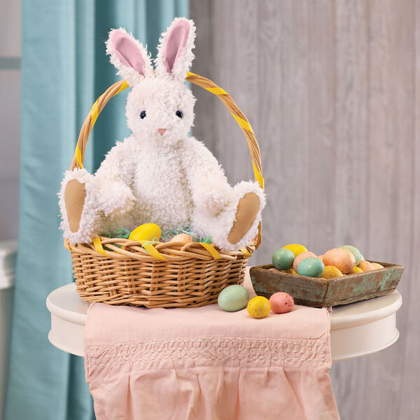 "16"" Classic Curly White Bunny  - Front view of jointed rabbit with blue eyes, pink nose and ears and beige foot pads sitting in an Easter basket surrounded by decorations - curly white fur image number 2"