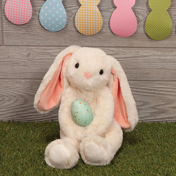 "15"" Buddy Bunny - Bunny Sitting with Easter egg in front of a wooden wall with Easter decorations image number 4"