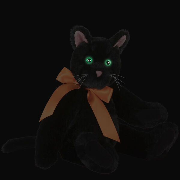 """15"""" Classic Black Cat - Front view of seated jointed cat with pink ears, black foot pads and green eyes dressed in an orange satin bow in the dark showing the eyes glowing - Black fur image number 1"""