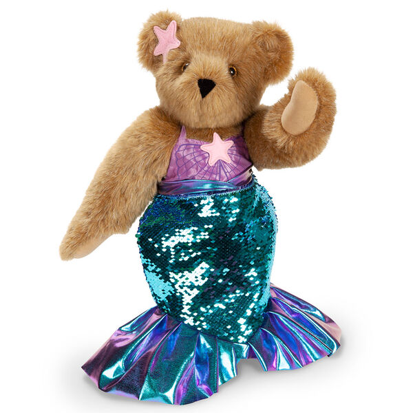 """15"""" Mermaid Bear - Three quarter view of standing jointed bear dressed in a blue sequin tail and purple top with shell embroidery an pink starfish applique and earpiece - honey brown fur image number 0"""