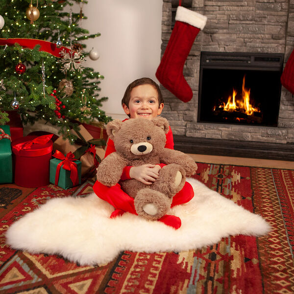 """18"""" Oh So Soft Teddy Bear - Front view of seated honey brown bear in a Christmas scene being held by a boy in pajamas image number 4"""