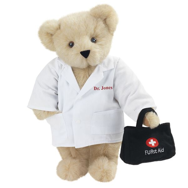 "15"" Doctor Bear - Front view of standing jointed bear dressed in white labcoat holding a doctor bag that is embroidered wth ""FURst Aid"" and a medical cross in red and white personalized with ""Dr. Jones"" on left chest in red - Buttercream brown fur image number 1"