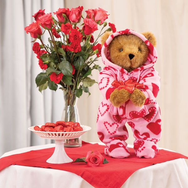 "15"" Hoodie-Footie Sweetheart Bear - Front view of standing jointed bear dressed in pink hoodie footie with red heart pattern on table with decorations - Honey brown fur image number 6"