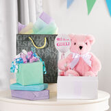 """11"""" New Baby Bear, Pink: Seated pink bear with white paw pads, brown eyes and white satin bow around neck in a birthday setting image number 1"""