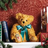 """15"""" Vintage Christmas Music Box Bear  - Front view of seated on a manteljointed bear with red and green Christmas wreath and musical clef embroidered on the right foot pad. Bear is wearing a green satin bow - Curly gold fur image number 1"""