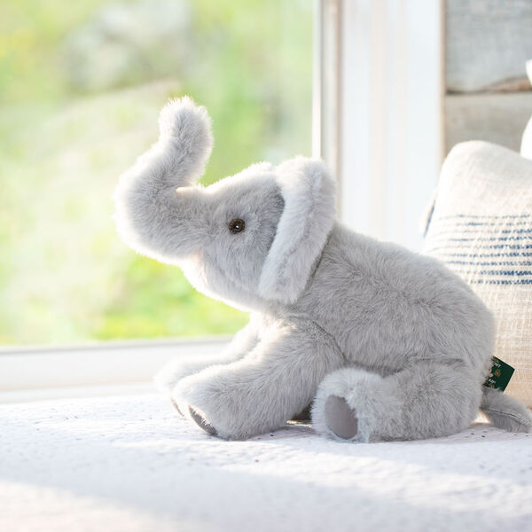 """15"""" Classic Elephant - Seated side view of gray plush elephant with upturned trunk and pink mouth looking out a window image number 8"""