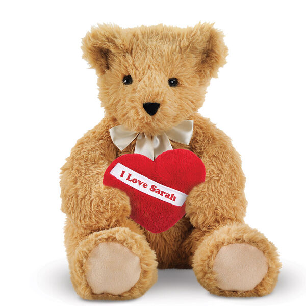 "20"" World's Softest Bear with Heart Pillow - 20"" seated golden brown bear with brown eyes holding a red fleece pillow with white diagonal sash. Pillow is personalized with ""I Love Sarah"" in red lettering. image number 1"