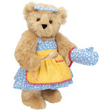 """15"""" Cooking Bear - Three quarter view of standing jointed bear dressed in a blue floral sundress and oven mitt, yellow apron with pink trim and holding a wooden spoon. Apron is personalized with """"Julietta"""" in hot pink - Maple brown fur image number 6"""