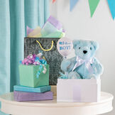 """11"""" New Baby Bear, Blue: Seated light blue bear with white paw pads, brown eyes and satin bow around neck in a birthday setting image number 1"""